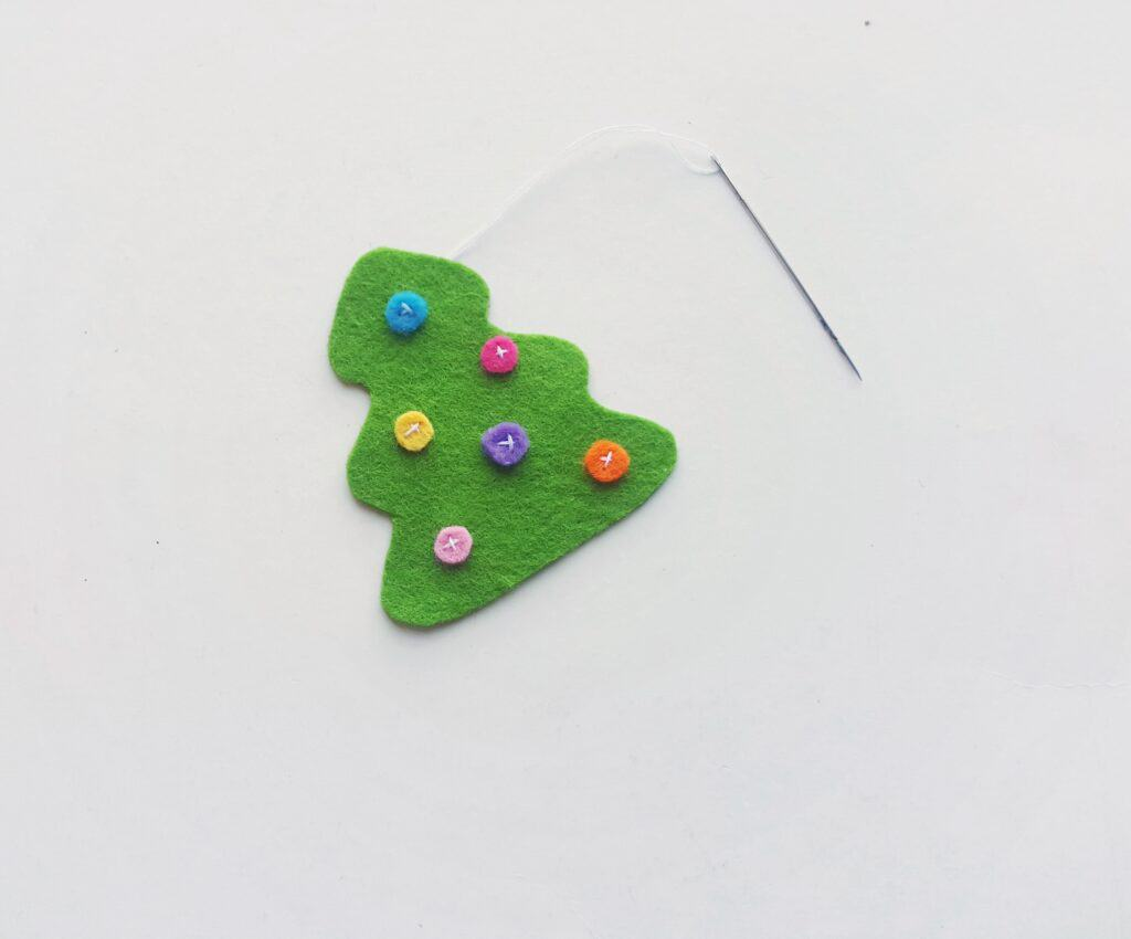 Sewing ornaments on felt Christmas tree