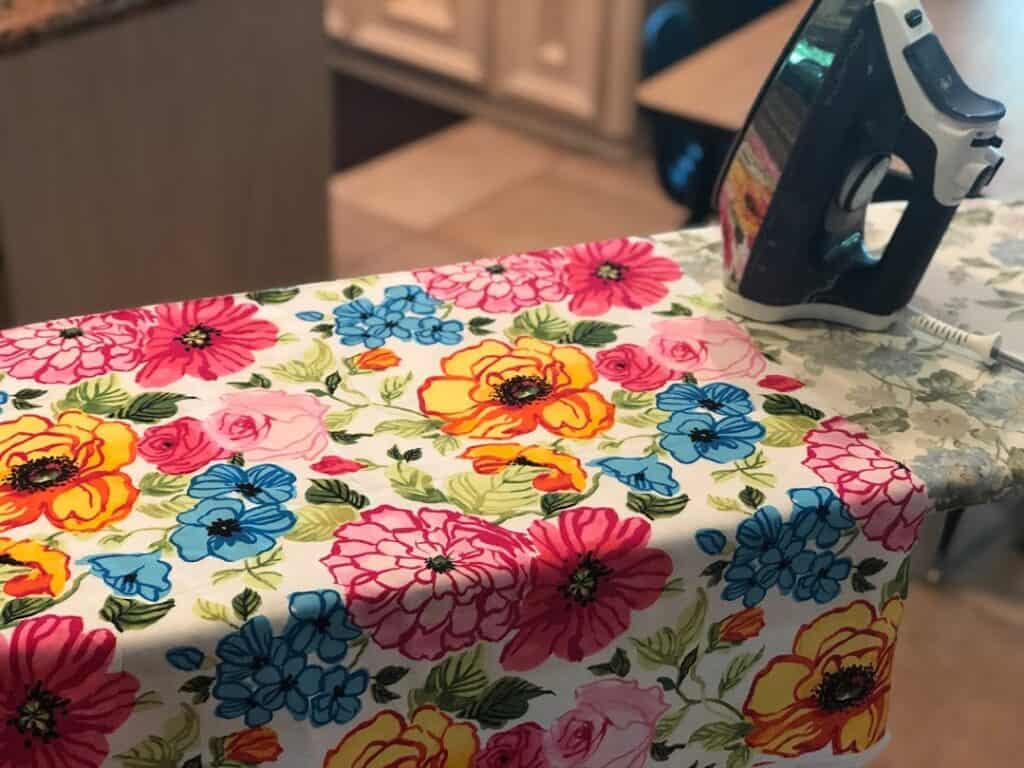 Ironing floral fabric on ironing board