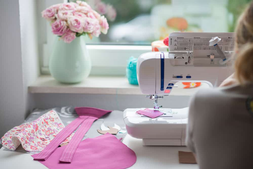 view of sewing room with sewing machine, fabric,, flowers and woman