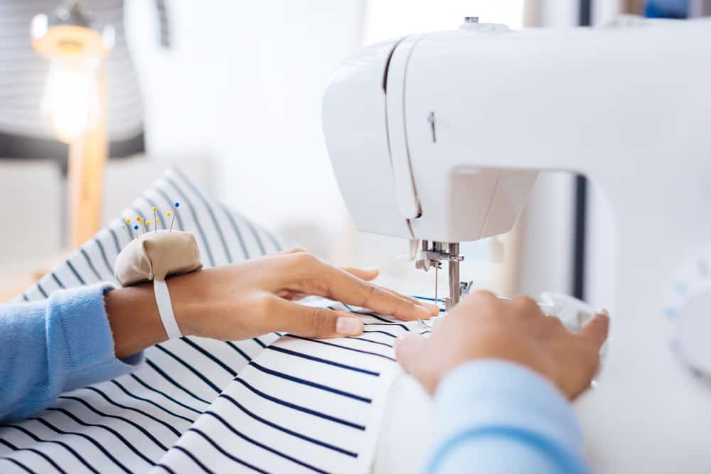Neat stitch. Skilled calm attentive worker of a professional atelier sitting in front of a modern sewing machine and creating a beautiful blouse