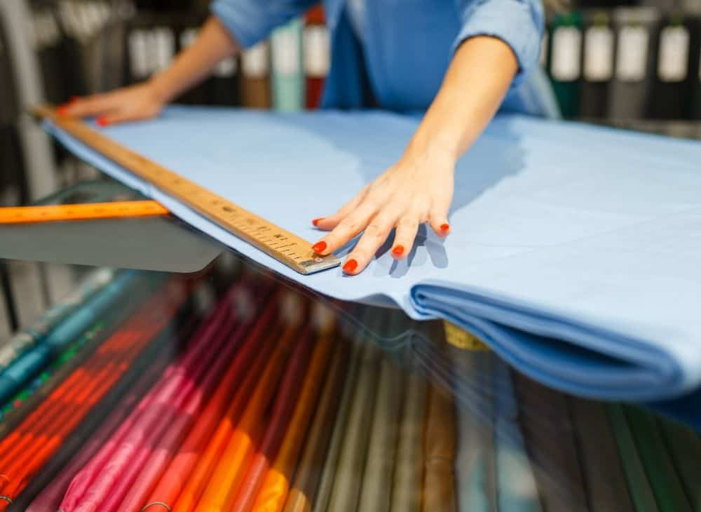 Woman measuring blue fabric with yard stick