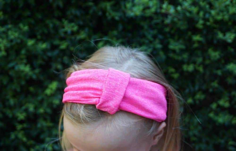 Girl with blond hair wearing hot pink knit headband with fabric knot