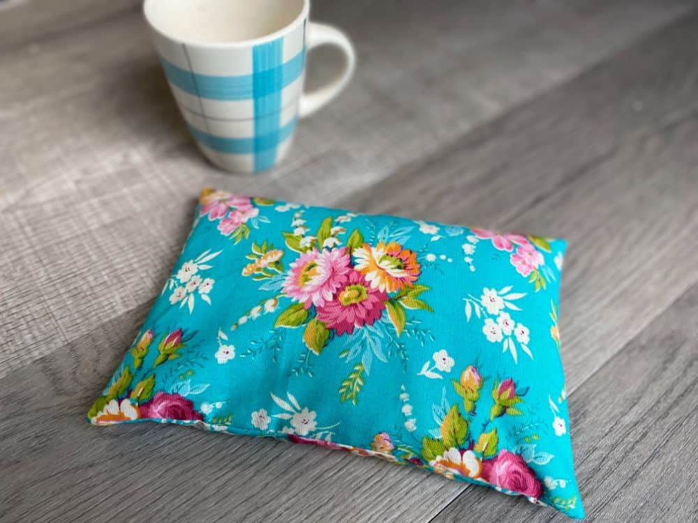 Homemade heating pad in floral fabric on table with coffee mug