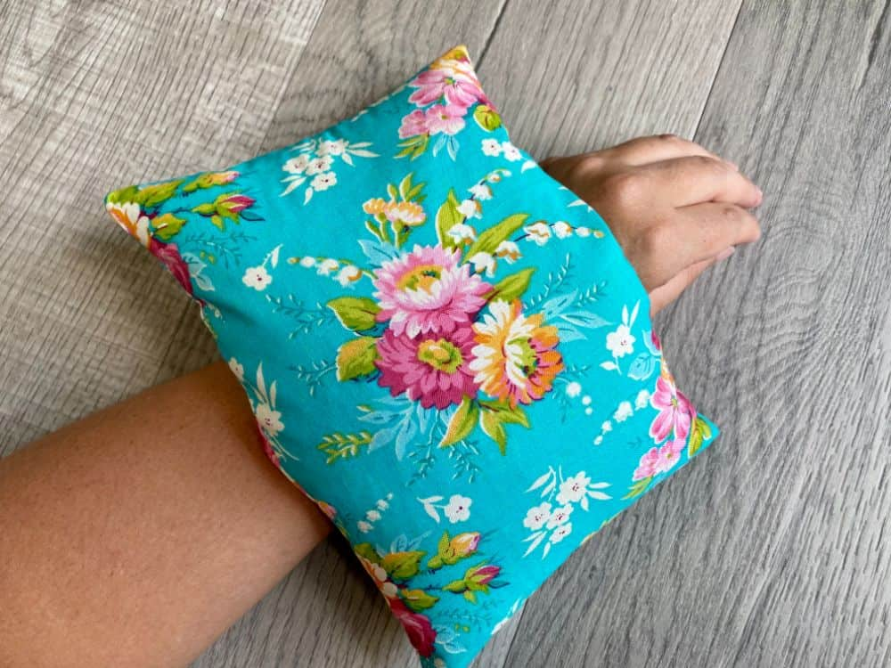Homemade heating pad made with floral fabric laying on wrist