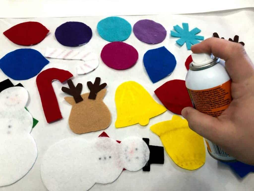 spraying back of felt ornaments with adhesive