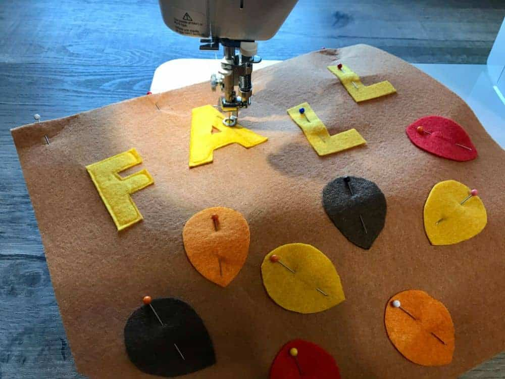 Sew on felt pieces to background