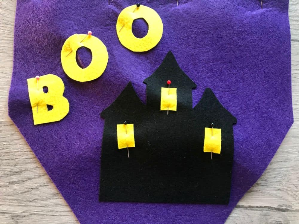 pin felt pieces to background of banner