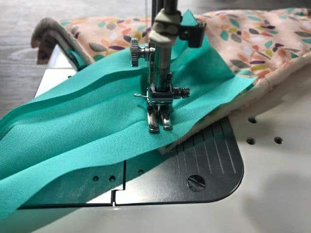 Sewing machine sewing bias tape to the corner
