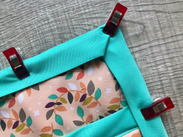 Closeup of folded corner of bias tape held with sewing clip