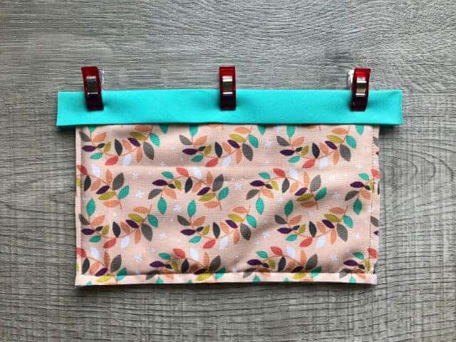 Double fold bias in teal color clipped across top of fabric rectangle and batting sandwich